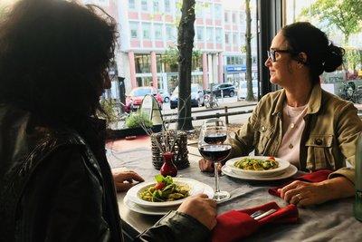 zwei Personen sitzen mit Essen an der offenen Fensterfront der Waschküche